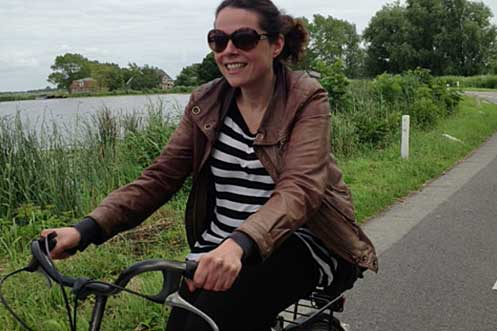 Cycling along the river Amstel in Amsterdam